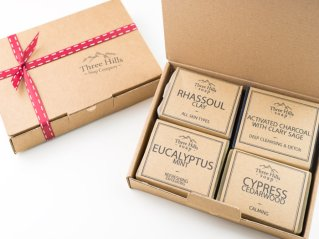 four handmade soaps in boxes