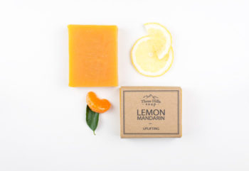 labelled and naked orange soap bars accompanied with real lemon and mandarin pieces