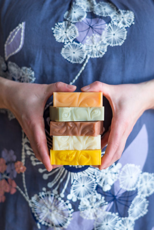 a woman holding natural soap bars